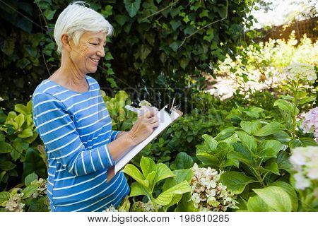 Side view of smiling senior woman writing on clipboard while standing amidst plants at backyard