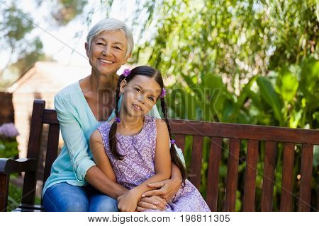 Portrait of smiling senior woman sitting with arm around girl on wooden bench at backyard