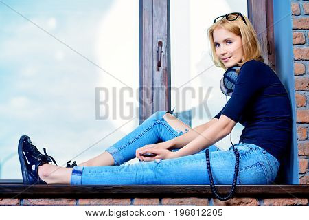 Happy young woman sitting at the window at home. Loft style interior.