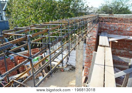 Unfinished Red Brick House Wall Under Construction without Roofing. Lintel Construction. Rebar steel bars on home construction reinforcement bars with wire rod as a lintel for window.