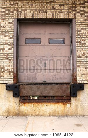 Close up on a rusty old metal truck loading dock door surrounded by brown brick on an old industrial warehouse.