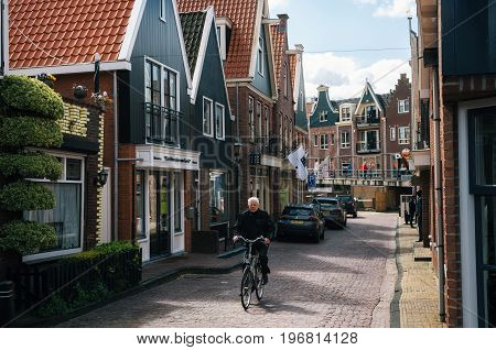 Volendam Netherlands - 26 April 2017: Resident of the village of Volendam by bike in front of the typical traditional houses of a Dutch fishing village Netherlands.