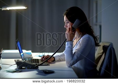 business, overwork, deadline and people concept - woman typing on laptop and calling on phone at night office
