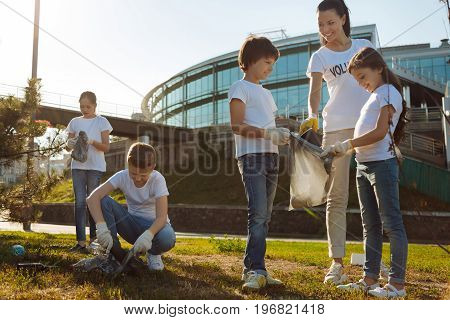 Lets start cleaning. Pretty coach helping her students in cleaning, little children keeping opened plastic bag while their friends gathering all rubbish
