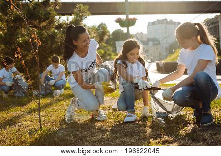 Be like us. Girls with their beautiful teacher sitting and gathering rubbish into plastic bag while other volunteers thinking of planets future