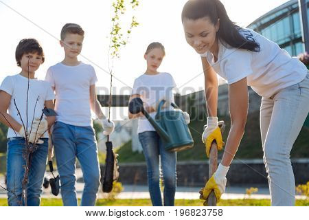 Repeat after me. Young leader preparing ground after cleaning for planting tree and her pupils standing, looking at process
