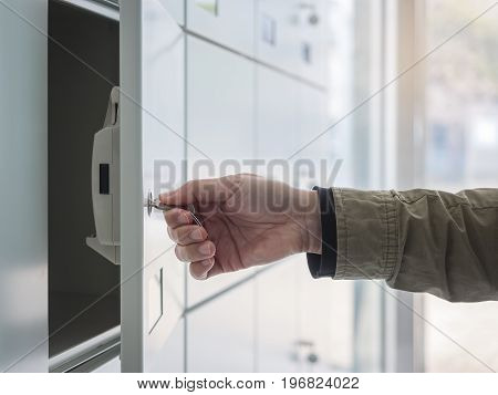 Hand with Key Open Locker in Locker room