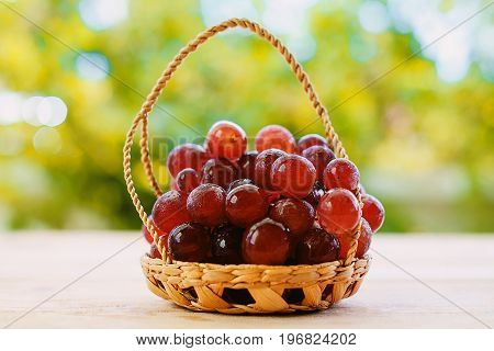 Red grape fruit in the basket on the wooden table with the natural blurred background