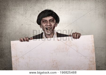Creepy And Bloody Asian Zombie Man Holding Empty Banner