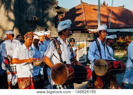 BALI INDONESIA - MARCH 07: Balinese traditional musicians play the gamelan at the ceremonial procession during Balinese New Year celebrations on March 07, 2016 in Bali, Indonesia.