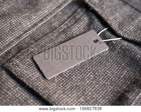 Blank label price tag on brown coat. Mockup for price or brand presentation.