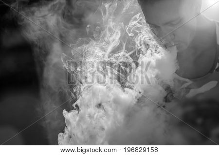 A handsome guy in military shirt is smoking ecigarette exhaling a cloud of vapor. Black and white photo.