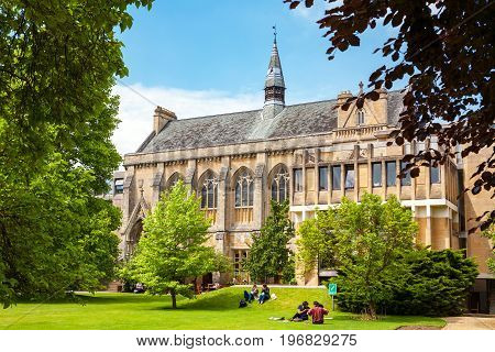OXFORD ENGLAND - JUNE 19 2013: Students relaxing on the grass outside Balliol College of Oxford University