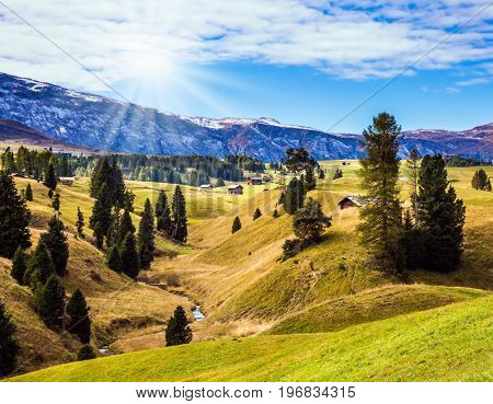 The famous winter ski resort. Autumn sun illuminates the hills. The landscape of the Alps di Siusi. The concept of an active and eco-tourism
