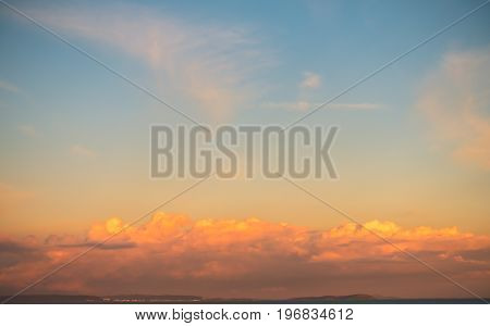 Cloudscape at sunset with beautiful illuminated clouds in golden and magenta colors with a blue sky.