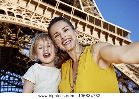 Happy Mother And Child Taking Selfie In Front Of Eiffel Tower