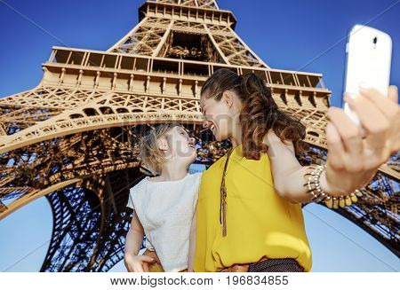 Mother And Daughter Tourists Taking Selfie Against Eiffel Tower