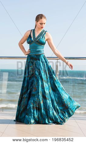 An elegant lady in a turquoise dress on a light blue sky background. A glamorous girl in a long dress is posing on a transparent balcony. A stylish woman on a hotel balcony near the sea.