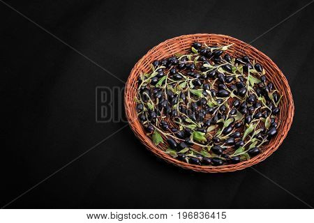 Sweet black currants and little green leaves in a wooden basket on a black background. A heap of rustic, ripe, raw and healthy black currants. Black berries for a gourmet breakfast.