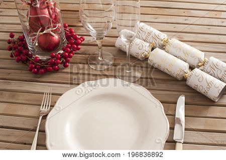 Festive table setting of white plate cutlery vine glasses with red berries decorations and wrapped candies over wooden outdoors table surface