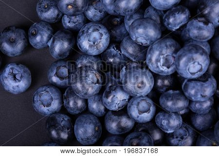 A macro picture of dark purple blueberries on a black background. Delicious and raw blueberries full of nutrients. Ingredients for light summer snacks. A group of freshly picked blueberries.