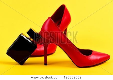 Red Female Shoes And Perfume Bottle On Yellow Background