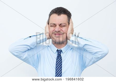 Closeup portrait of tensed middle-aged business man covering ears and closing his eyes tight. Isolated front view on white background.