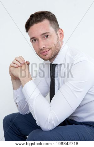 Confident handsome young male entrepreneur with clasped hands looking at camera. Smiling successful manager in formalwear sitting and leaning on knees. Business portrait concept
