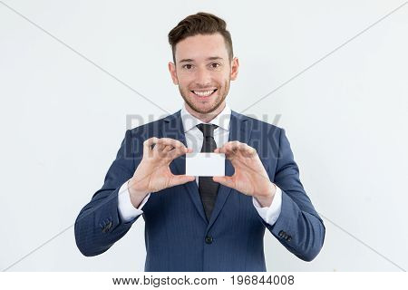 Successful male financial advisor showing blank card and looking at camera. Cheerful handsome businessman sharing his contacts. He running own company. Investor concept