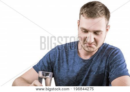An unsatisfiable man is drinking medications, isolated on a white background. The man in a dark blue T-shirt is taking prescription drugs. Medicine.