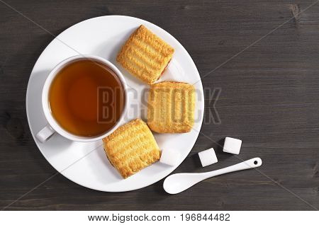 Cup of tea and shortbread cookies with jam in plate on dark table for breakfast top view