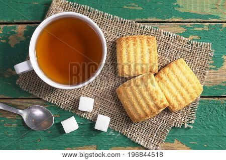 Cup of tea and shortbread cookies with jam on old green background top view