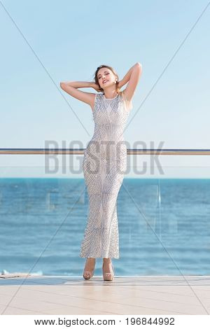 Full-length photo of a lady in a long and shiny white dress near the sea. The cute young lady enjoying on a sunny glass balcony on a saturated blue sea background. Elegance, beauty, fashion concept.