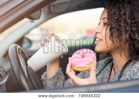 Woman eating a sweet and drinking driving her car