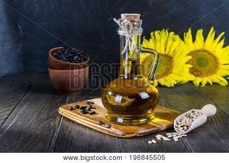 Still life with sunflower oil in glass bottle, seed and sunflower on the background of wooden boards