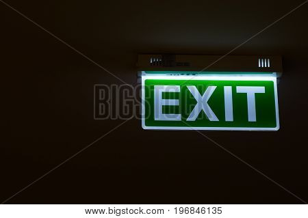 Exit sign hanging on the ceiling with glowing green light.