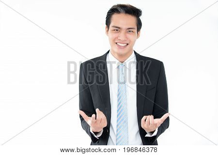 Portrait of joyful young Asian businessman gesturing to camera. Emotional handsome guy being successful in business. Playful man showing hand sign expressing uncertainty. Modern business concept