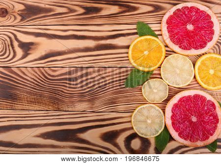 Top view of juicy and ripe citrus fruits with green leaves of mint on a wooden background. Slices of exotic and sour lemon, sweet orange and juicy grapefruit with leaves of mint on the right side, close-up.