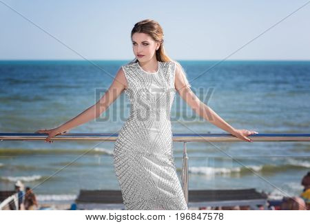 A charming lady on a bright blue noisy sea background. The pretty female in a loose white dress with patterns on the hotel's balcony. The good-looking girl in fantastic dress near the sea.