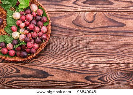A composition of tasty gooseberries with green leaves in a brown basket on a dark wooden table. A bright brown crate with nutritious gooseberries. A basket full of delicious berries.