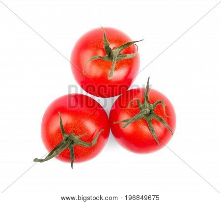 Three whole, fresh and bright red tomatoes with green leaves isolated on a white background. Summer tomatoes for salads. Harvest of vegetables full of vitamins. Organic tomatoes from a garden.