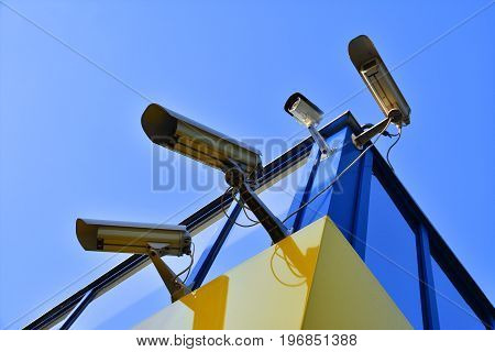 four surveillance cameras on the corner of the building