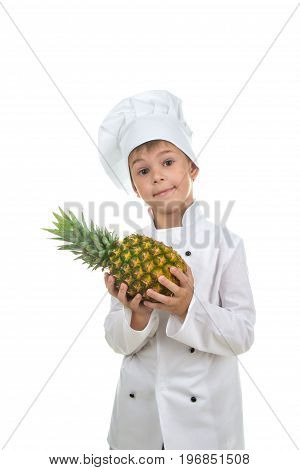 Handsome teen boy wearing chef uniform holding ananas. Portrait of a happy cute male child cook with fresh pineapple, isolated on white background. Food and cooking concept.