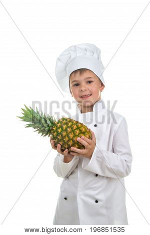 Handsome happy boy wearing chef uniform holding ananas. Portrait of a happy cute male child cook with fresh pineapple, isolated on white background