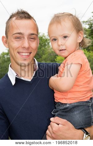 Smiling Father With Little Daughter In His Arms