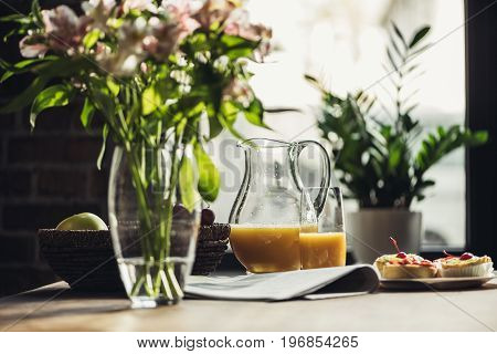 Still Life Of Newspaper, Flowers And Breakfast With Cakes And Juice On Kitchen Table In Front Of Win