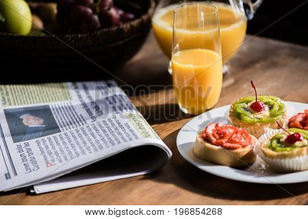Still Life Of Newspaper, Breakfast With Cakes And Glass Of Juice On Kitchen Table