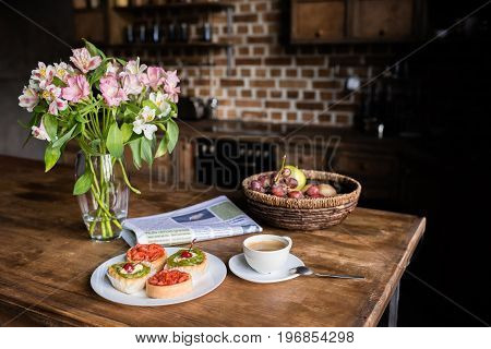 Still Life Of Flowers, Newspaper, Breakfast With Cakes, Coffee And Fruits On Kitchen Table