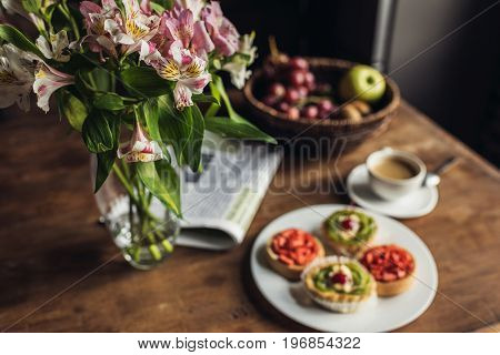 Still Life Of Newspaper, Flowers And Breakfast With Cakes And Hot Coffee On Kitchen Table In Front O