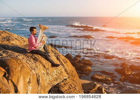 Young musician play the trumpet on rocky sea coast during surf. Tuba instrument.